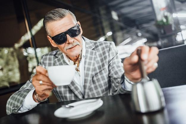 モダンなカフェのサマーテラスでコーヒーを飲むsolideシニア。