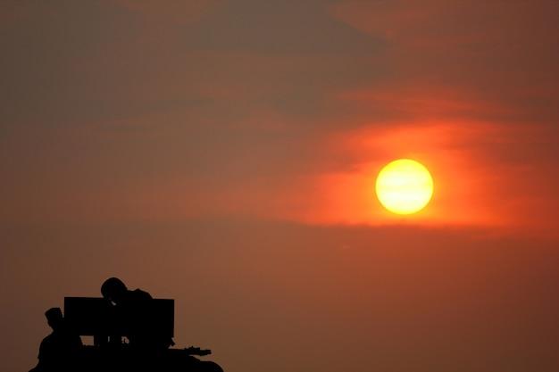 군인은 태양 세트 아름다움 하늘 추상 자연 배경으로 군사 기관총에 의해 대기