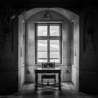 A solitaire chair and table in an ampty room of castle savoia, building in typical walsen architectural style.
