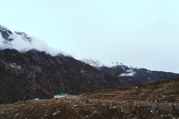 Solitary building by the mountains with a pakistani flag