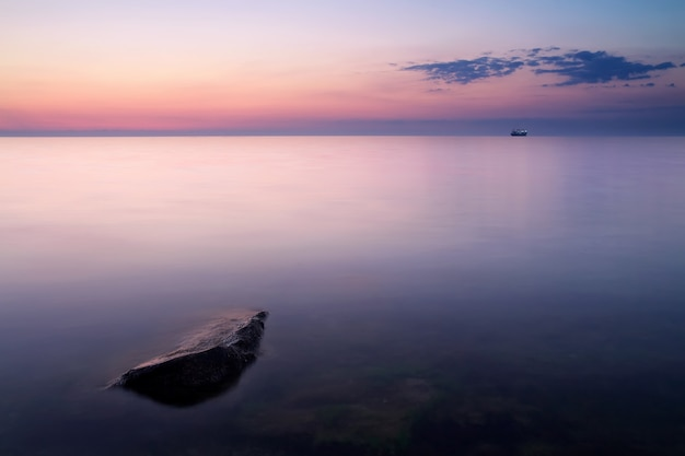 Solitary stone on seashore during sundown