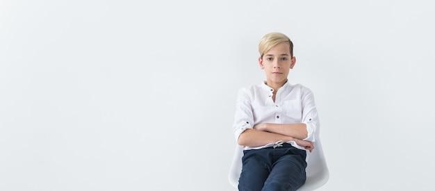 Концепция одиночества, одиночества и скуки - скучающий студент-подросток, сидящий в школьном стуле, изолированном на белом фоне