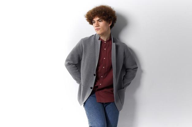 孤独、孤独、悲しみの概念。物思いにふける表情で、後ろに手を握って灰色の壁にもたれかかって、ずんぐりした服を着た悲しい思いやりのある若い男のクロップドショット
