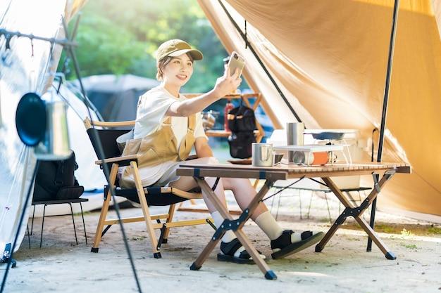 솔로캠프 이미지 - 스마트폰으로 셀카를 찍는 여성