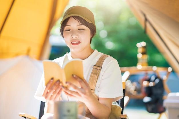 ソロキャンプの画像-本を読んでいる若い女性