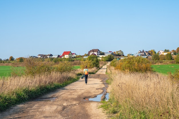 一人旅のコンセプト。秋の田舎道、ハイキング旅行を歩いているバックパックを持つ女性の背面図。ロシア。