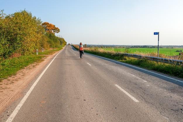 一人旅のコンセプト。秋の田舎道、ハイキング旅行を歩いているバックパックを持つ女性の背面図。