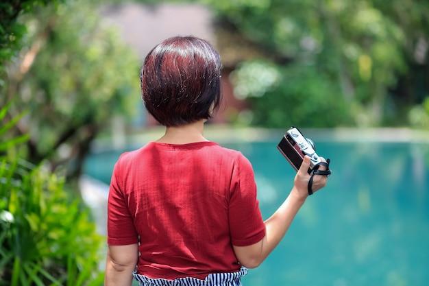 호텔 리조트에서 휴식을 취하는 솔로 여행 여성 관광객