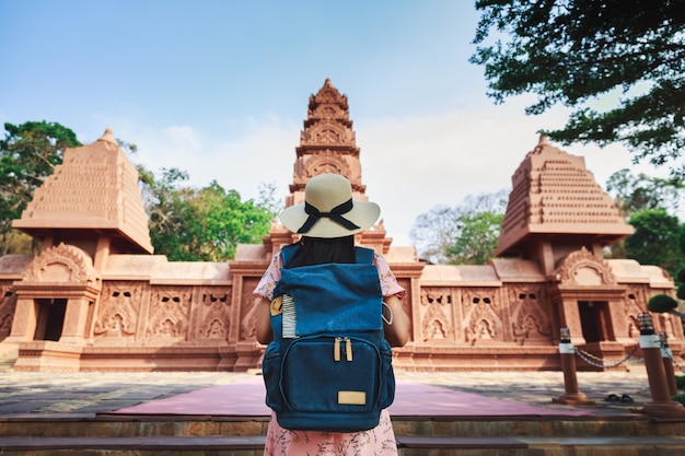 Одиночное путешествие расслабляет концепцию отпуска, молодой счастливый азиатский путешественник и фотограф женщина с камерой и рюкзаком осматривает достопримечательности в храме ват тхам пху ва, канчанабури, таиланд
