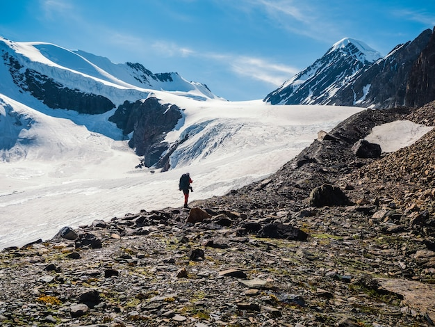 山でのソロトレッキング。男性のハイカーが山道を下っていきます。背景には、雪をかぶった大きな山々。