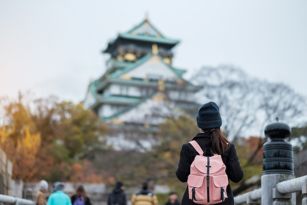 秋の大阪城を旅する一人の女性観光客、日本の大阪市を訪れるアジア人旅行者。休暇、目的地、旅行のコンセプト