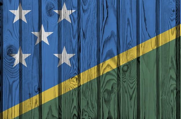 Флаг соломоновых островов изображен в яркие краски цвета на старые деревянные стены.