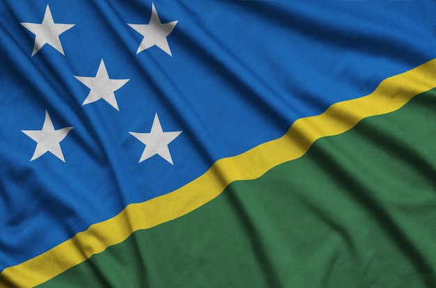Флаг соломоновых островов изображен на спортивной ткани с множеством складок.