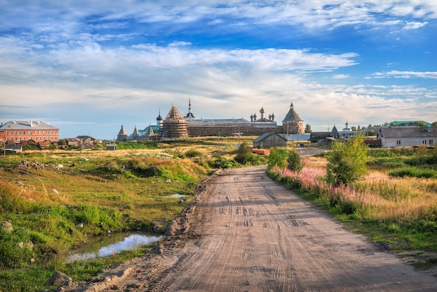 ソロヴェツキー修道院と夕日の光の中の草の間の未舗装の道路