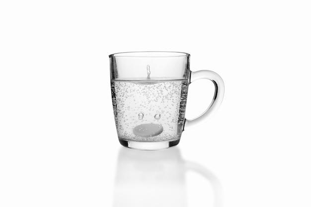 Растворимая газированная таблетка упала в прозрачную стеклянную кружку на белой поверхности.