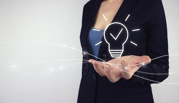 솔루션 분석 및 개발, 혁신적인 기술 개념. 회색 배경에 디지털 홀로그램 벌프 램프를 들고 있습니다. 창의적인 새로운 아이디어. 혁신, 브레인스토밍, 영감 및 솔루션.