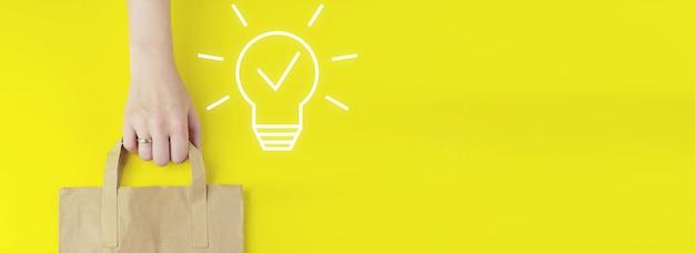 솔루션 분석 및 개발, 혁신적인 기술. 노란색 배경에 홀로그램 벌프 아이콘이 있는 재활용된 갈색 종이 쇼핑백, 평평한 위치. 창의적인 아이디어입니다. 개념 아이디어와 혁신입니다.