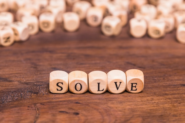 Solve word on wooden cubes over brown table