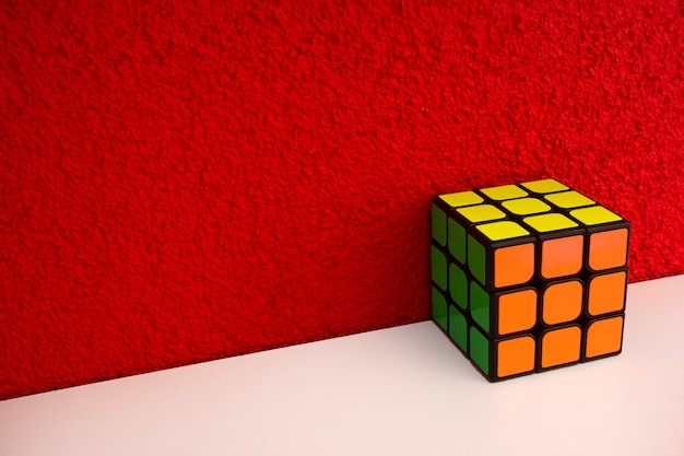 Solved puzzle speed cube on white wooden shelf near red colored wall colorful rubiks cube with copy ...