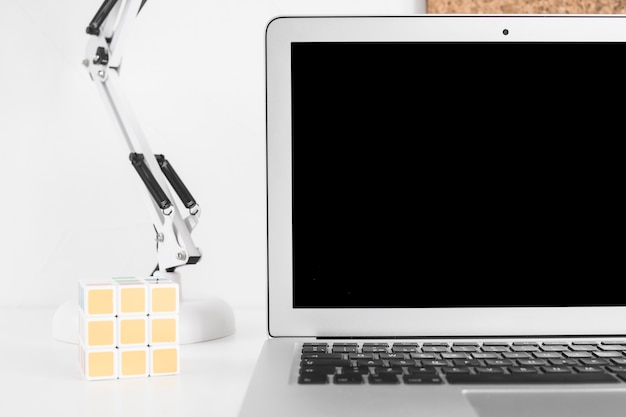 Solved rubik cube with laptop on white background