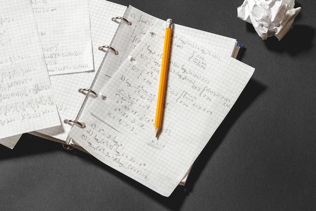 노트북에서 수학적 문제를 해결합니다. 검은 책상에 구겨진 종이 조각.