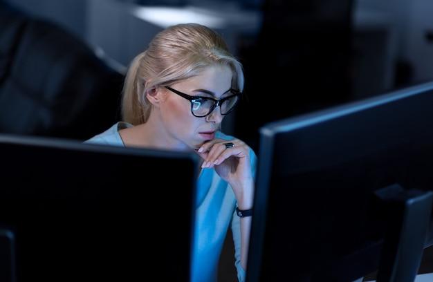 어려움을 해결합니다. 온라인 암호 코드를 해결하는 동안 사무실에 앉아서 컴퓨터를 사용하는 자신감있는 숙련 된 프로그래머