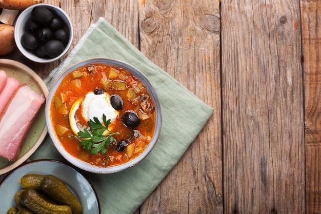 Солянка, русский суп с колбасой, оливками, маринованными огурцами и каперсами. вид сверху