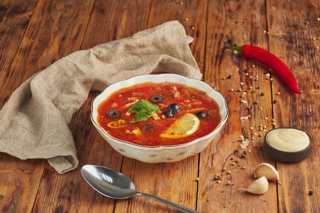 Солянка - традиционный русский мясной суп. русский суп солянка в круглой тарелке на деревянном столе