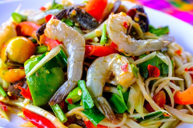 Som tam seafood (spicy papaya salad) with salted crab, on wooden table ( thai food)