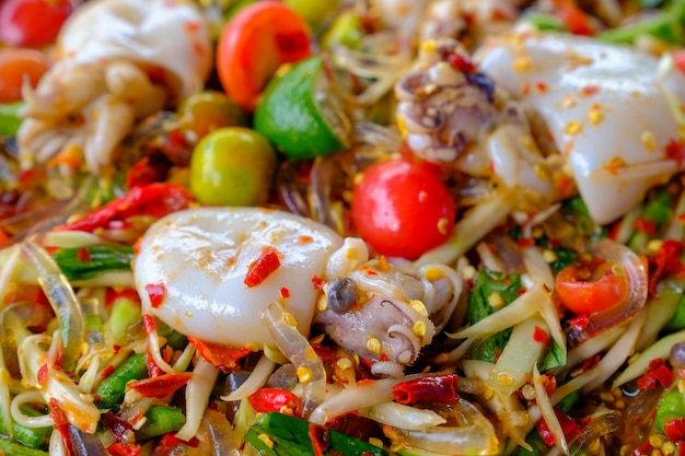 Som tam seafood (spicy papaya salad) with salted squid, on wooden table ( thai food)