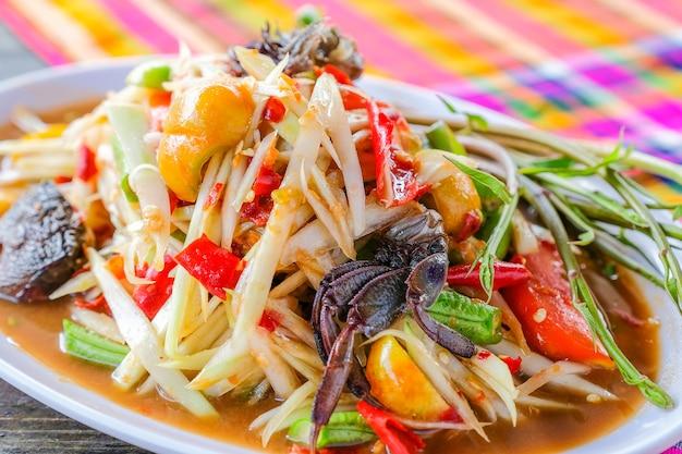 Som tam (пряный салат papaya) с соленым крабом, на деревянном столе (тайская кухня)