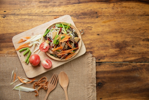 Som tam thai, thai papaya salad on wooden background