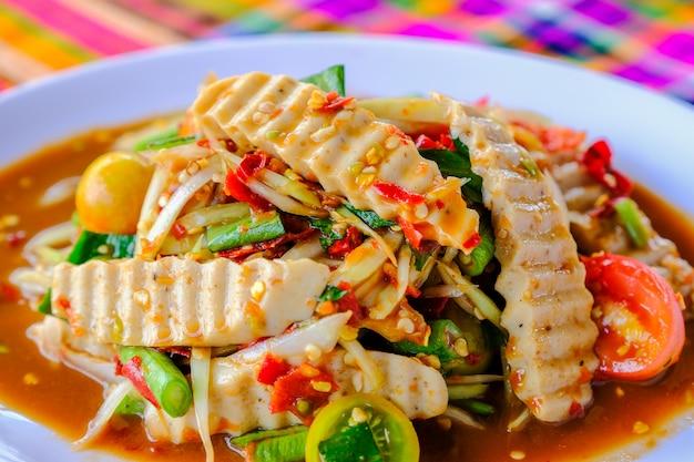 Som tam вьетнамская свиная колбаса (пряный салат papaya) с соленым крабом, на деревянном столе (тайская кухня)