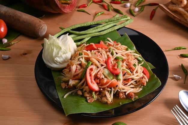Тум сом или салат из зеленой папайи в плите. тайская концепция еды.