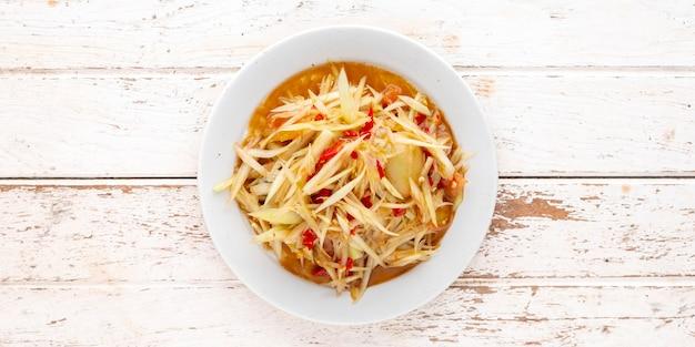 Som tum pla ra, тайская еда e-san, острый салат из папайи с маринованной рыбой, помидорами, лаймом и чили в белой керамической тарелке на белом фоне текстуры древесины с копией пространства для текста, вид сверху