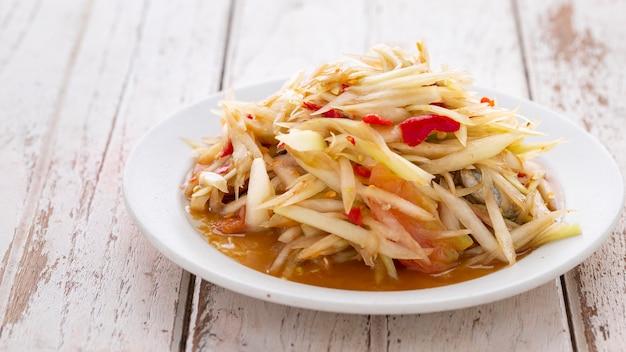 Som tum pla ra, тайская еда e-san, острый салат из папайи с маринованной рыбой, помидорами, лаймом и чили в белой керамической тарелке на белом фоне текстуры древесины с копией пространства для текста