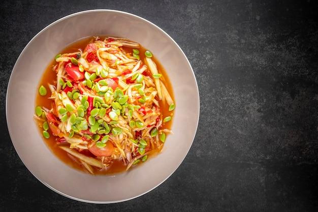 ソムタム、ソムタム、タイのe-sanフード、ピクルスの魚、トマト、ライム、唐辛子のスパイシーなパパイヤサラダ、ダークトーンのテクスチャ背景にファタキンシードをトッピング、上面図
