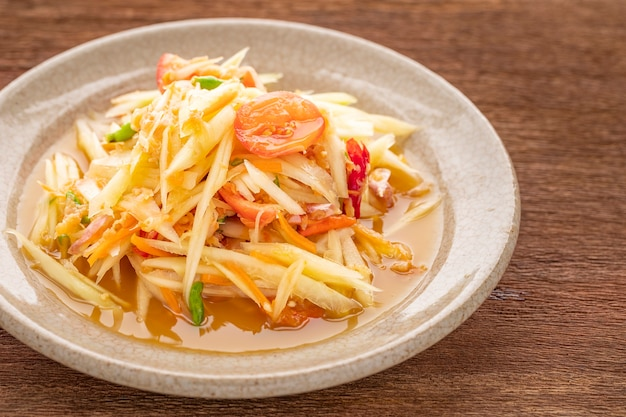 ソムタムタイ、ソムタムタイ、タイ料理、スパイシーなパパイヤサラダ、トマト、ライム、唐辛子のトッピング、干しエビ、天然木の質感の背景、上面図