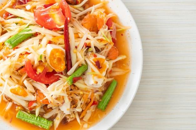 ソムタム-塩辛い卵とタイのスパイシーなグリーンパパイヤサラダ-アジア料理のスタイル