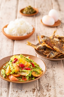 Сом тум туа, там туа, тайская кухня, салат из острой длинной фасоли с хрустящей жареной рыбой, вареным рисом, вареными яйцами и острым соусом для макания на старом белом фоне деревянной текстуры