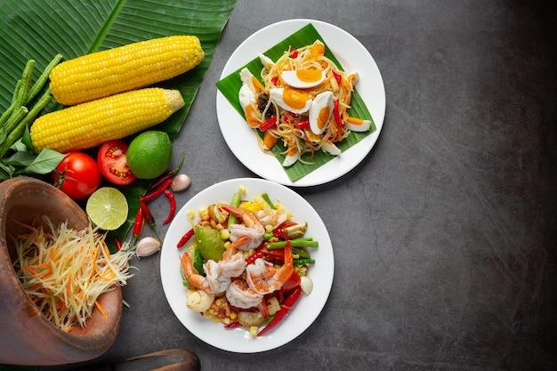 Сом тум с кукурузой и креветками, подается с рисовой лапшой и зеленым салатом. украшен ингредиентами тайской кухни.