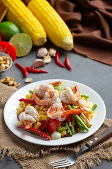 Som tum with corn and shrimp, served with rice noodles and green salad decorated with thai food ingredients.