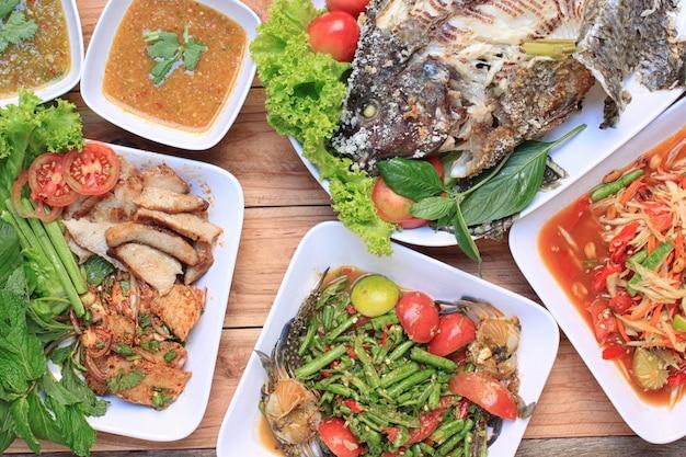 Коллекция тайской еды на деревянном полу, салат папайи (som tum).