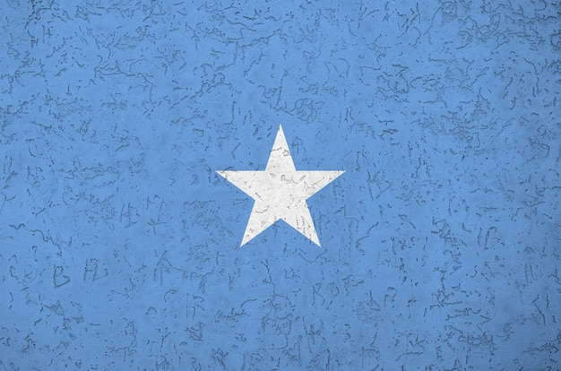 Somalia flag depicted in bright paint colors on old relief plastering wall.