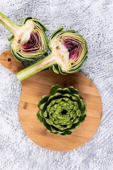 Some artichoke and slices on a cutting board, on light gray background, high angle view.