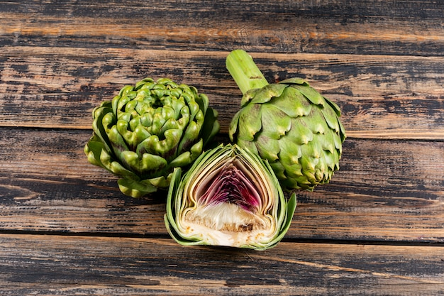 Some artichokes and a slice on dark wooden background, flat lay.