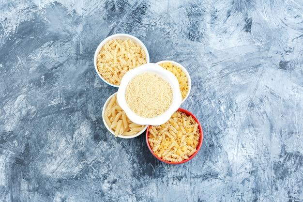 Alcuni assortiti di pasta in ciotole su intonaco grigio sfondo, vista dall'alto.