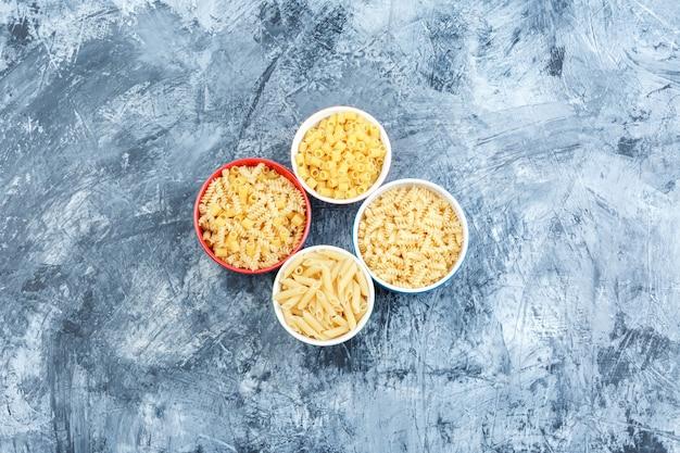 Alcuni assortiti di pasta in ciotole su una schifezza di sfondo intonaco, piatto laici.