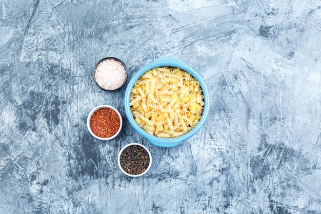 Alcuni assortiti di pasta con spezie in una ciotola su sfondo grigio intonaco, vista dall'alto.