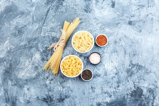Alcuni assortiti di pasta con spezie in ciotole su intonaco grigio sfondo, vista dall'alto.
